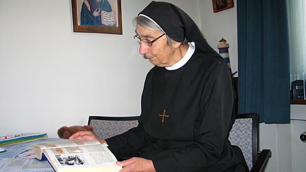 Schwester Liliane Juchli blättert in einem Buch.