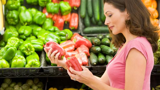 Frau vor Gemüseregal