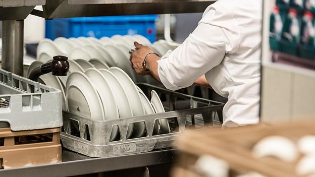 Angestellter eines Gastrobetriebes beim Geschirrwaschen.