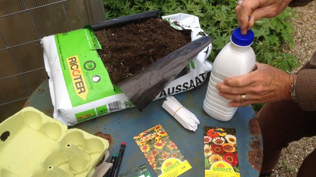 Blumenerde, Eierkarton, Giesskanne aus Milchflasche