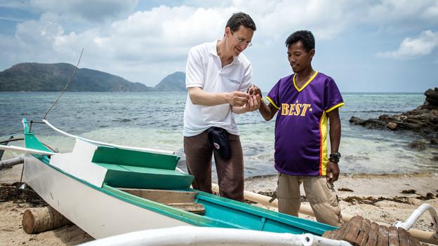 SRK-Direktor Markus Mader lässt sich von einem Fischermann auf der philippinischen Insel Busuanga / Region Palawan die Fischerei-Technik erklären.