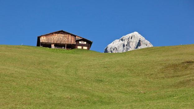 Maiensäss in den Alpen vor blauem Himmel.