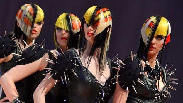 Frauen mit bunten Haaren und schrägen Frisuren.