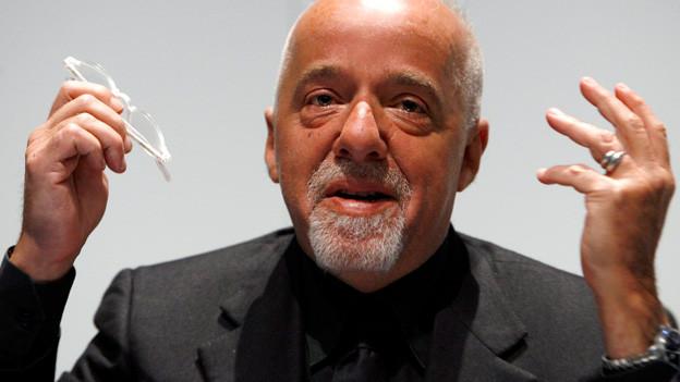 Paulo Coelho gestikuliert mit seiner Brille