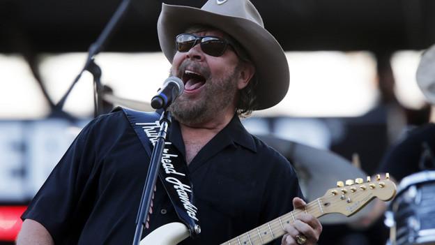 Hank Williams Jr. mit Cowboy-Hut und Gitarre auf der Bühne