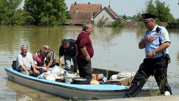 Menschen retten sich im Boot vor dem Hochwasser.