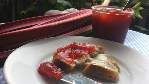 Frühstücksteller mit Konfi-Brot, im Hintergrund ein Glas mit Rhabarber-Konfitüre und frische Rhabarber.