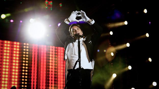 Robbie Williams formt auf der Bühne seine Hände zum Herz.