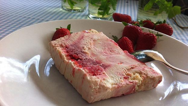 Erdbeer-Holunderblüten-Parfait auf Tisch garniert mit Erdbeeren.