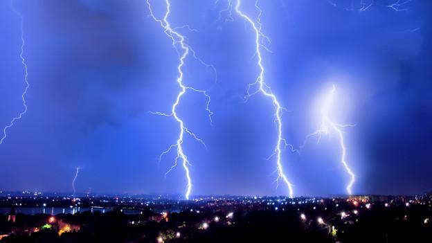 Blitze am Nachthimmel über einer Stadt.