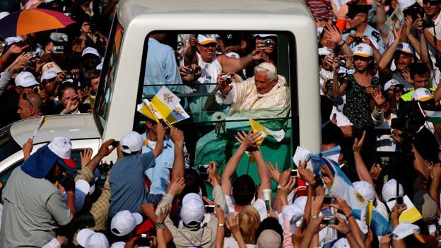 Papst im Papamobil fährt durch fotografierende Masse.