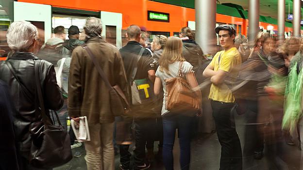 Pendler stehen vor dem Zug.
