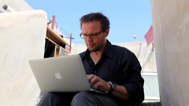 Kurt Pelda auf einem Dach in Syrien mit Laptop auf dem Schoss.