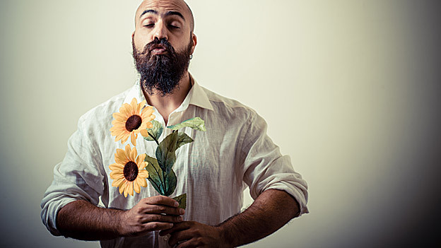 Mann mit Vollbart und Blumen in der Hand.