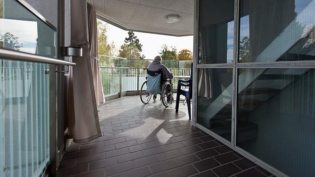 Alte Frau im Rollstuhl auf dem Balkon eines Pflegeh