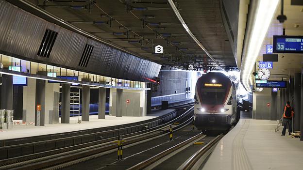 Ein Zug fährt in den neuen unterirdischen Bahnhof ein.