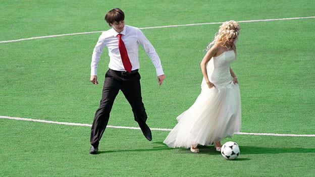 Junges Hochzeitpaar am Fussaball spielen