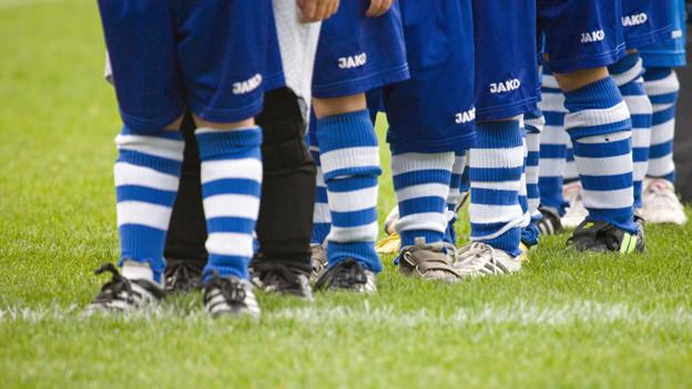 Die Beine von jungen Fussballern auf dem Rasen.