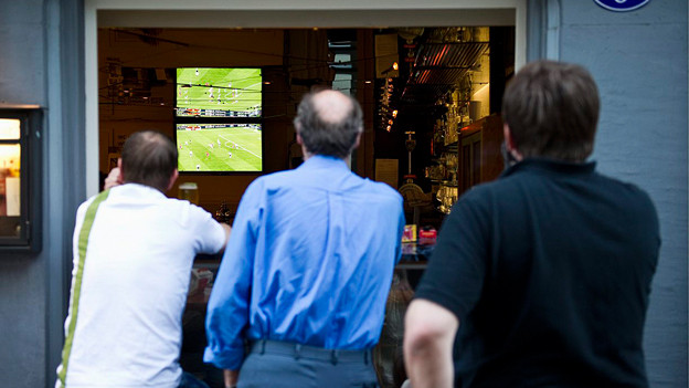 Drei Männer schauen bei einem Restaurant von draussen aufs Fussballspiel, das im TV läuft.