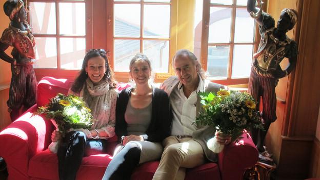Gastgeberin zwischen den beiden Gästen auf einem rosaroten Sofa.