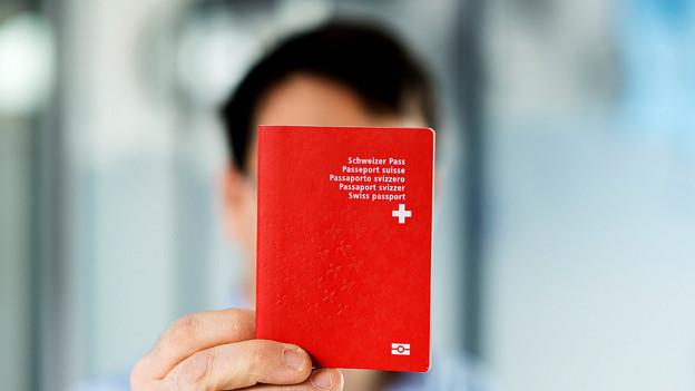 Mann hält Schweizer Pass vor sich.