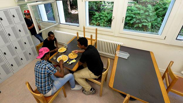 Flüchtlinge essen am Tisch im Asylzentrum Hirschplatz in Luzern.