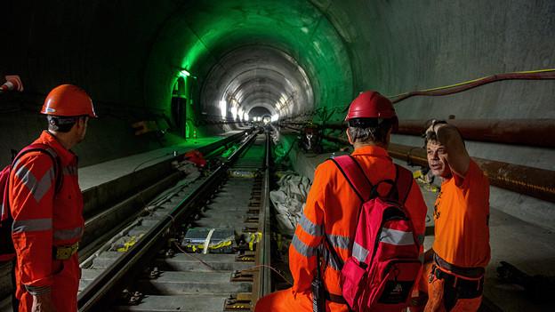 Drei Arbeiter bei der Arbeit im Tunnel.