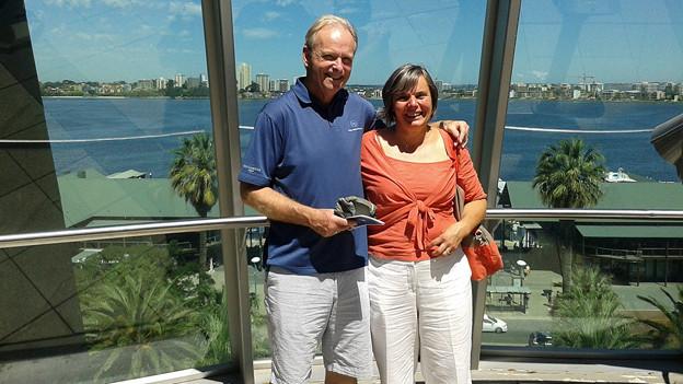 Anita Dick und ihr Ehemann posieren vor einer Glaswand, dahinter Wasser und Palmen.