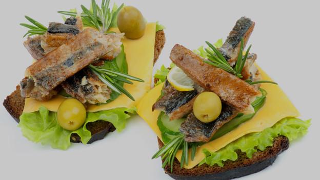 Mediterrane Canapés mit Fisch, Oliven und Rosmarin.
