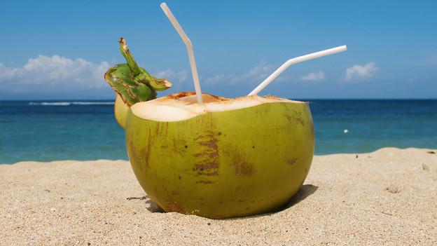 Eine grüne Kokosnuss mit zwei Strohhalmen im Sand, dahinter das Meer.