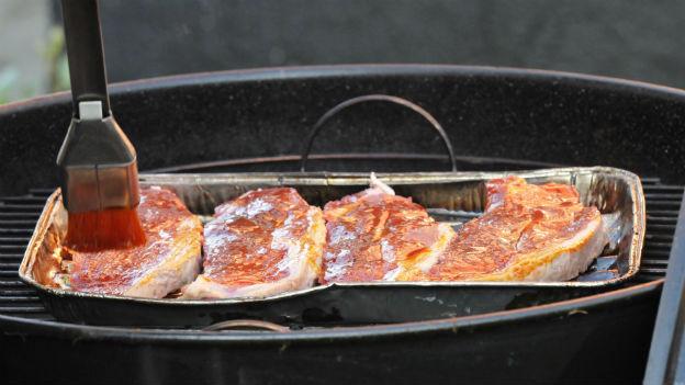 Fleisch wird auf Grill gebraten und mit Pinsel mariniert