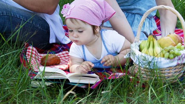 Ein Kleinkind mit seinen Eltern auf der Picknick-Decke.