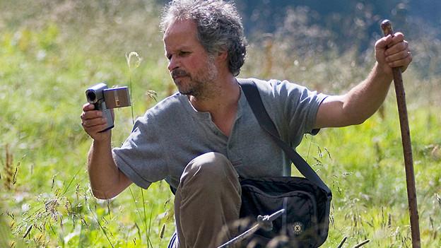Giorgio Hösli mit Stock und Kamera in einer Alpwiese.