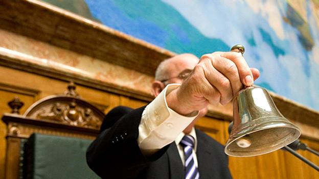 Politiker läutet die Glocke der Session.