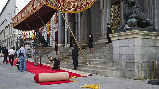 Arbeiter rollen den roten Teppich aus.