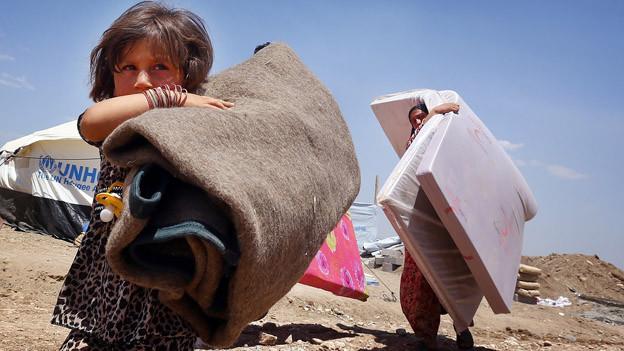 Flüchtlinge mit Matratze und Decken