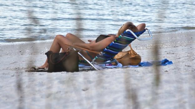 Frau in einem Liegestuhl am Strand.