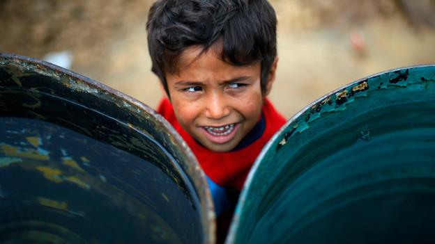 Flüchtlingskind hinter Tonnen.