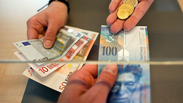 Geldwechsel von Euro und Franken am Schalter.