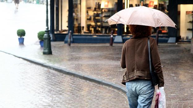Frau mit Regenschirm in Einkaufsstrasse.