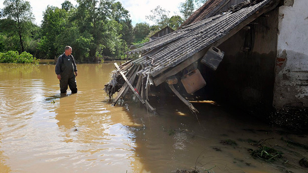 Ein Mann steht in den Fluten und betrachtet ein Haus, das vom Hochwasser zerstört worden ist.
