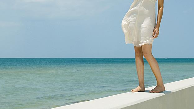 Frau mit weitem Kleid am Meer.