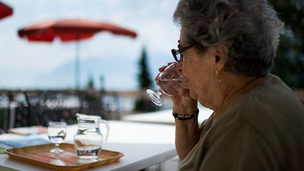 Seniorin trinkt Wasser.