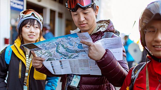 Chinesische Touristen schauen Schweizer Karte an.