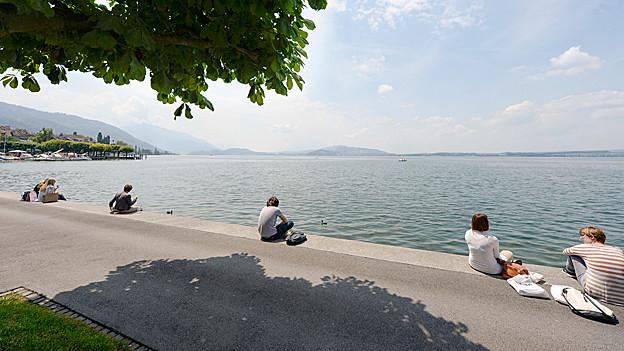 Menschen geniessen den Sommer am See.