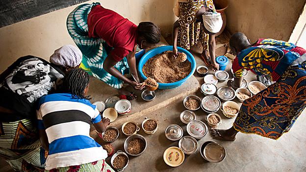 Frauen aus Burkina Faso bücken sich über Gefässe.