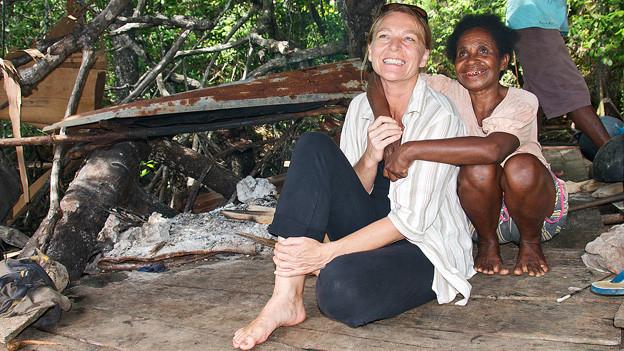Maja Hadorn kniet mit einer Frau aus dem Nachbardorf Kabui.
