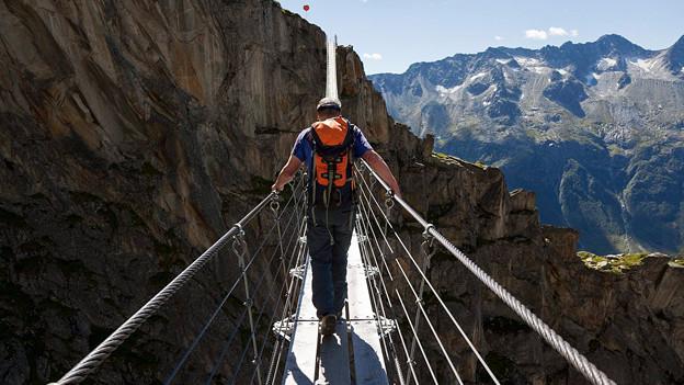 Ein Wanderer auf einer Hängebrücke im Hochgebirge.