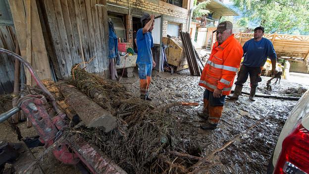 Arbeiter in den Hochwasser-Trümmern auf einem Bauernhof.