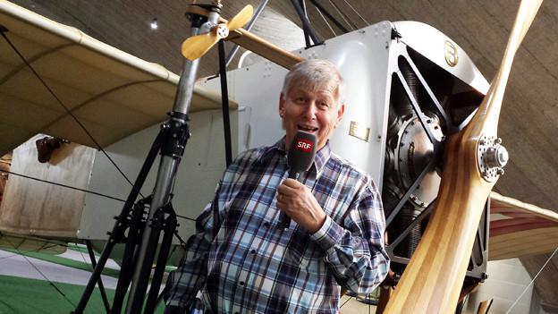 Fliegermuseums-Führer Rudolf Wicki vor einem alten Flugzeug..